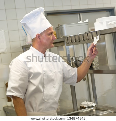 Chef in uniform reading orders in restaurant's kitchen