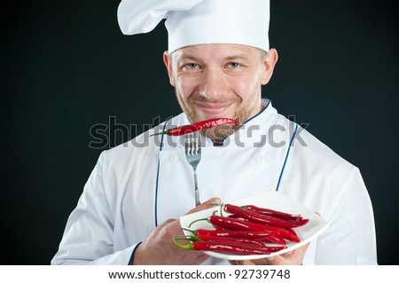 Chef in uniform with a plate of chili peppers smiling and looking at camera - stock photo