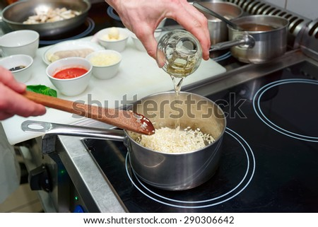 Chef is adding white wine to risotto, copy space - stock photo