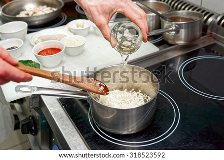 Chef is adding white wine to risotto, toned image - stock photo