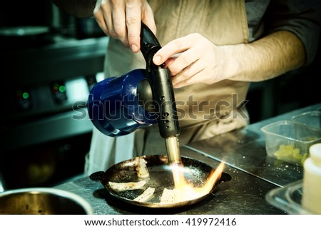 Chef is burning onion slices with gas burner, toned image