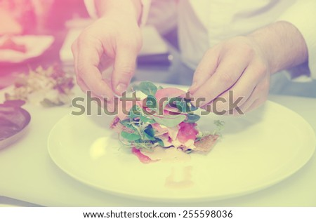 Chef is cooking appetizer on professional kitchen, toned image - stock photo