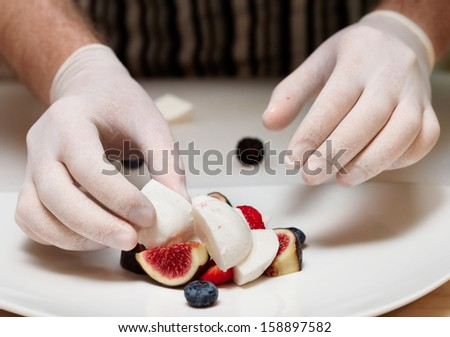 Chef is cooking salad with mozzarella, figs and berries - stock photo
