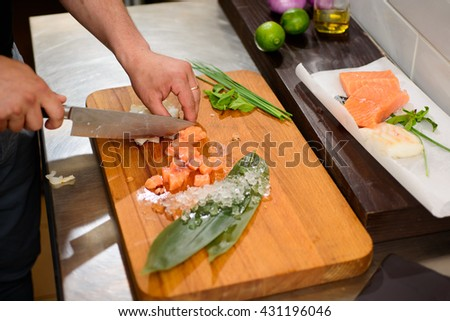 Chef is cooking salmon ceviche on commercial kitchen