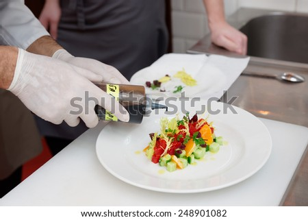 Chef is cooking tuna appetizer, adding balsamic vinegar - stock photo