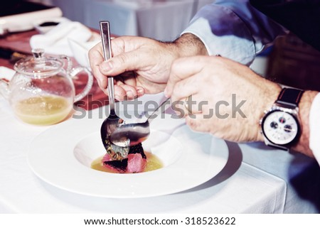 Chef is cooking tuna appetizer, toned image - stock photo