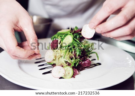 Chef is decorating appetizer with lettuce mix, toned image - stock photo