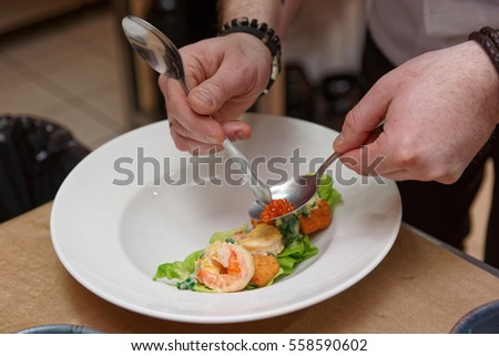 Chef is decorating prawn appetizer with salmon roe, commercial kitchen, slight motion blur