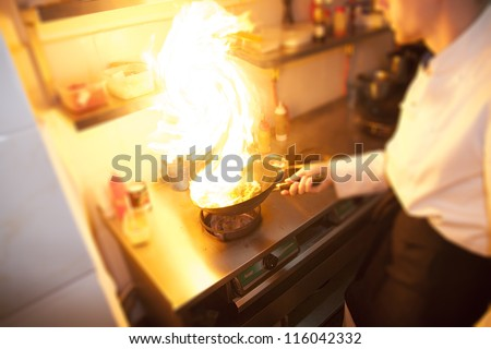 Chef is making flambe with pan and fire - stock photo