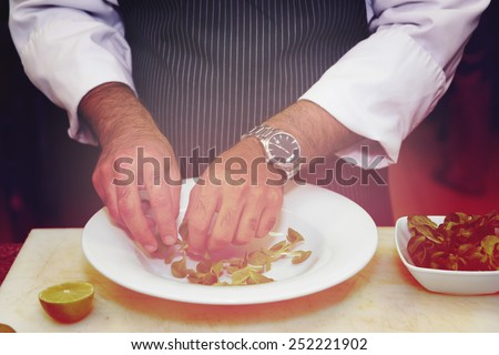 Chef is mixing salad at professional kitchen, toned picture - stock photo