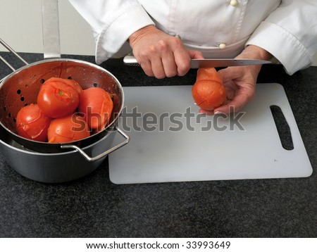 Chef is peeling boiled tomatos - stock photo