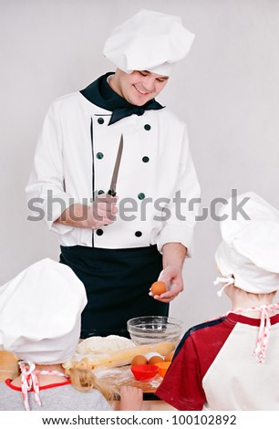 Chef is teaching kids to cook on the grey background - stock photo