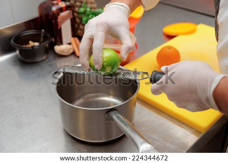 Chef is zesting lime in bowl, commercial kitchen - stock photo