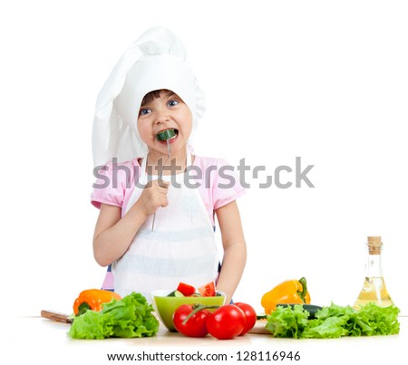Chef kid preparing and tasting healthy food over white background - stock photo