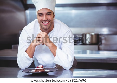 Chef leaning on the counter with a dessert in commercial kitchen - stock photo