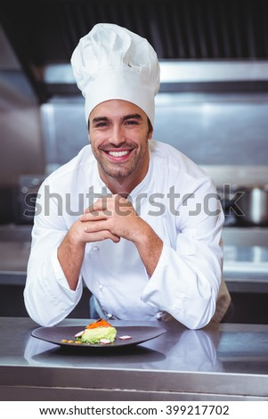 Chef leaning on the counter with a dish in a commercial kitchen - stock photo
