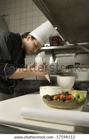 Chef leaning over a cake concentrating as he decorates it with icing. There is a fruit plate next to it. Vertically framed photo. - stock photo