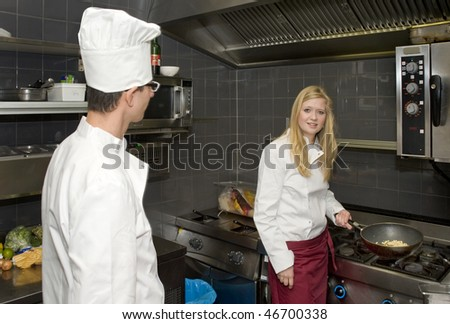 Chef looking at his assistant in a professional kitchen - stock photo