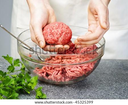 Chef making hamburgers in kitchen with ground beef - stock photo