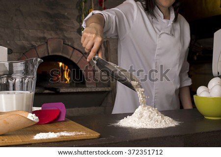 Chef making pile of flour in front of a pizza oven in a restaurant kitchen. - stock photo