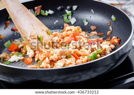 chef making  stir fried onion, tomato, green bell pepper and chicken on frying pan