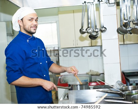 chef man in uniform boiling a soup on cooker in kitchen - stock photo
