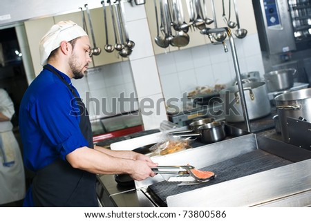 chef man in uniform frying a fish slice on grill in kitchen - stock photo