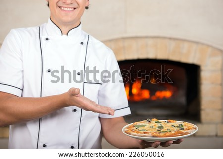 Chef offers to you delicious pizza. Close-up.