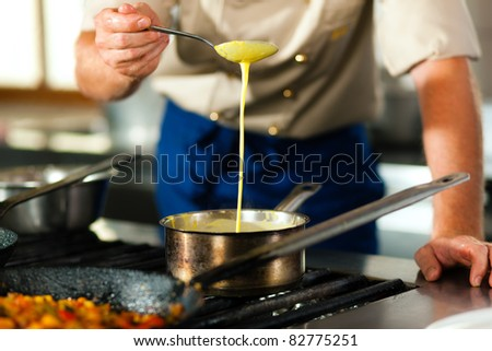 Chef - only torso to be seen - in a restaurant or hotel kitchen cooking; he is preparing the sauce