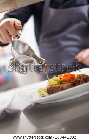 Chef plating up food in a restaurant pouring a gravy or sauce over the meat before serving it to the customer, close up view of his hand and the gravy boat - stock photo