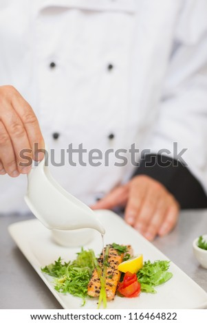 Chef pouring sauce on salmon in the kitchen - stock photo