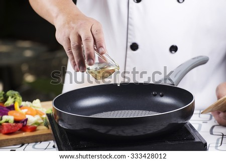 Chef pouring vegetable oil to the pan / Stir fried vegetable concept - stock photo
