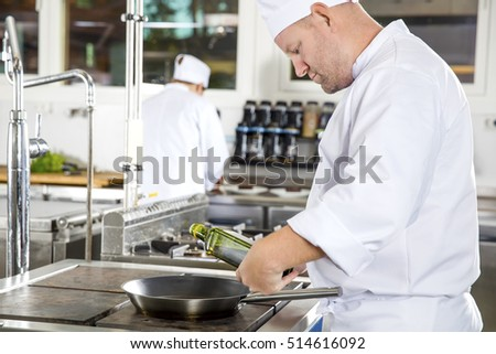 Chef pours olive oil in pan at a professional kitchen