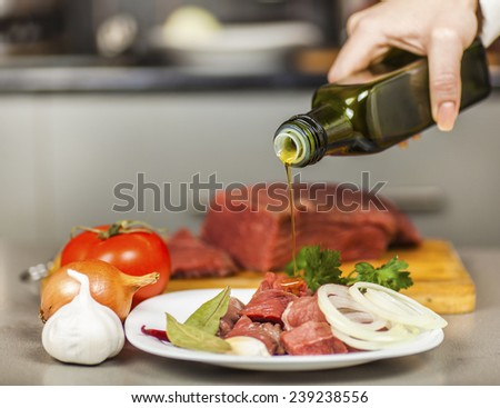 Chef pours olive oil on meat fillet