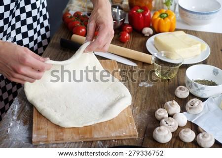 Chef prepare the dough for home made pizza - stock photo