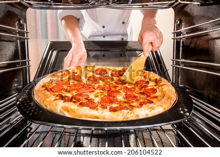 Chef prepares pepperoni pizza in the oven, view from the inside of the oven. Cooking in the oven.