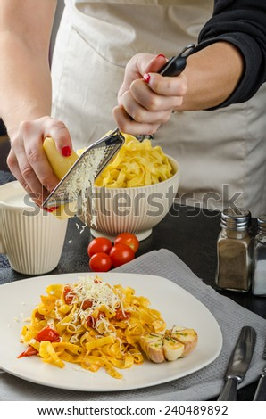 Chef prepares - tagliatelle with cherry tomatoes and roasted garlic bio