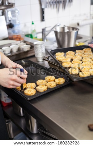 Chef preparing desserts removing them from individual ramekins or moulds and placing them out on a tray in a commercial kitchen - stock photo