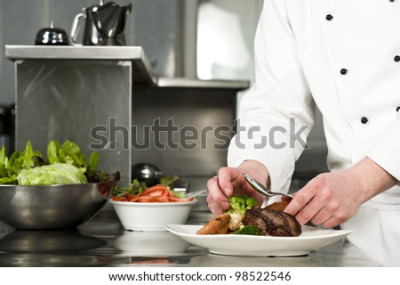 Chef preparing meal (steak with croquette) - stock photo