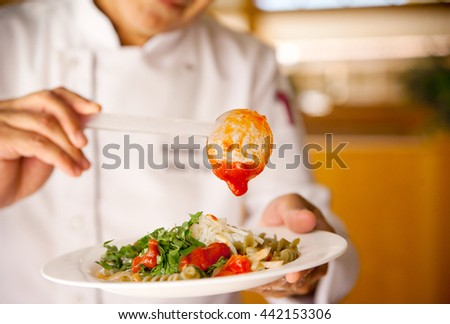 Chef preparing pasta with tomato sauce, cheese and herbs