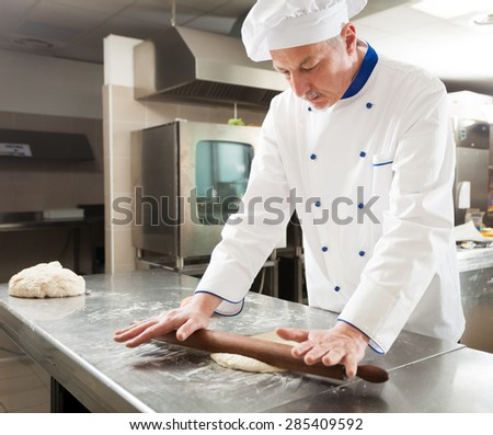 Chef preparing pastry in his kitchen - stock photo