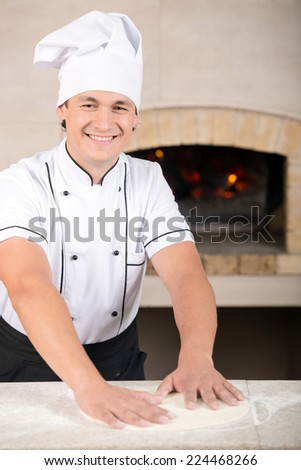 Chef preparing pastry in his kitchen. The oven on the background.