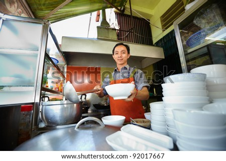 Chef preparing traditional Asian street food and working in the restaurant kitchen. Horizontal shape, front view - stock photo
