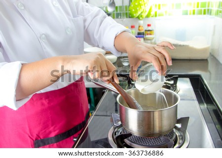 Chef put the milk for preparing food in pot - stock photo