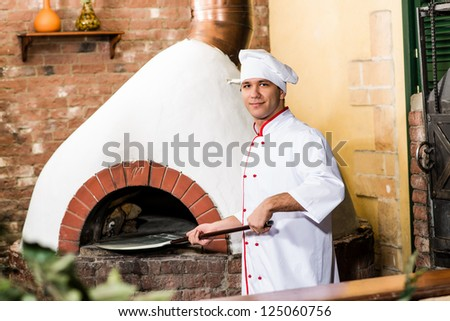 Chef puts dough in the oven for pizzas, traditional cooking - stock photo