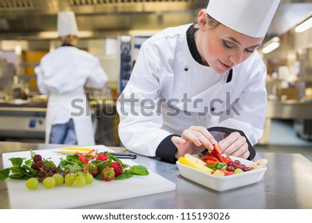 Chef putting a strawberry in the fruit salad in the kitchen - stock photo