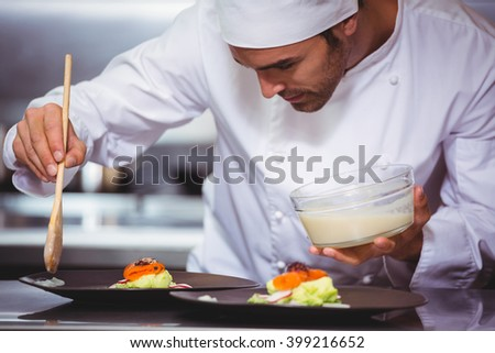 Chef putting sauce on a dish in a commercial kitchen - stock photo