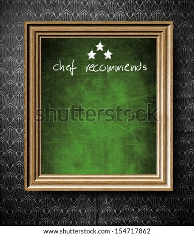 Chef recommends with copy-space chalkboard in old wooden frame on vintage wall - stock photo