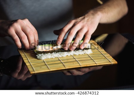 Chef rolling up sushi on a bamboo mat. - stock photo
