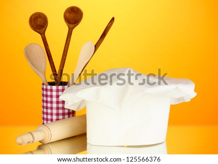Chef's hat with spoons and battledore on orange background - stock photo